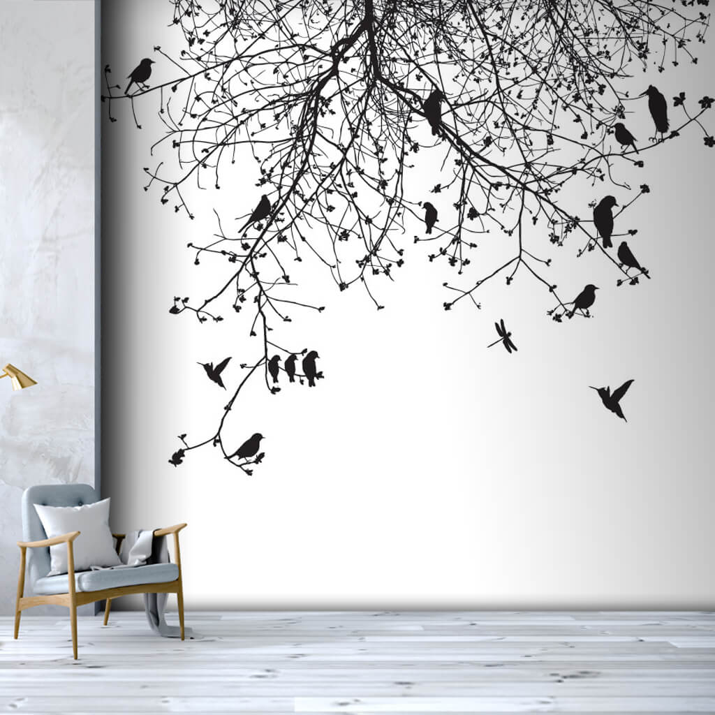 Birds flying among black white tree branches wall mural
