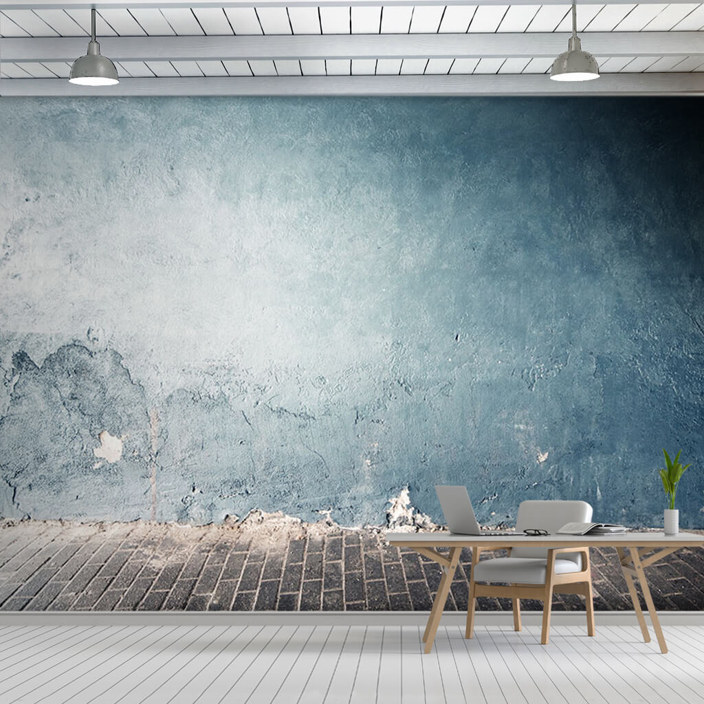 Blue plastered concrete wall front of cobblestone wall mural