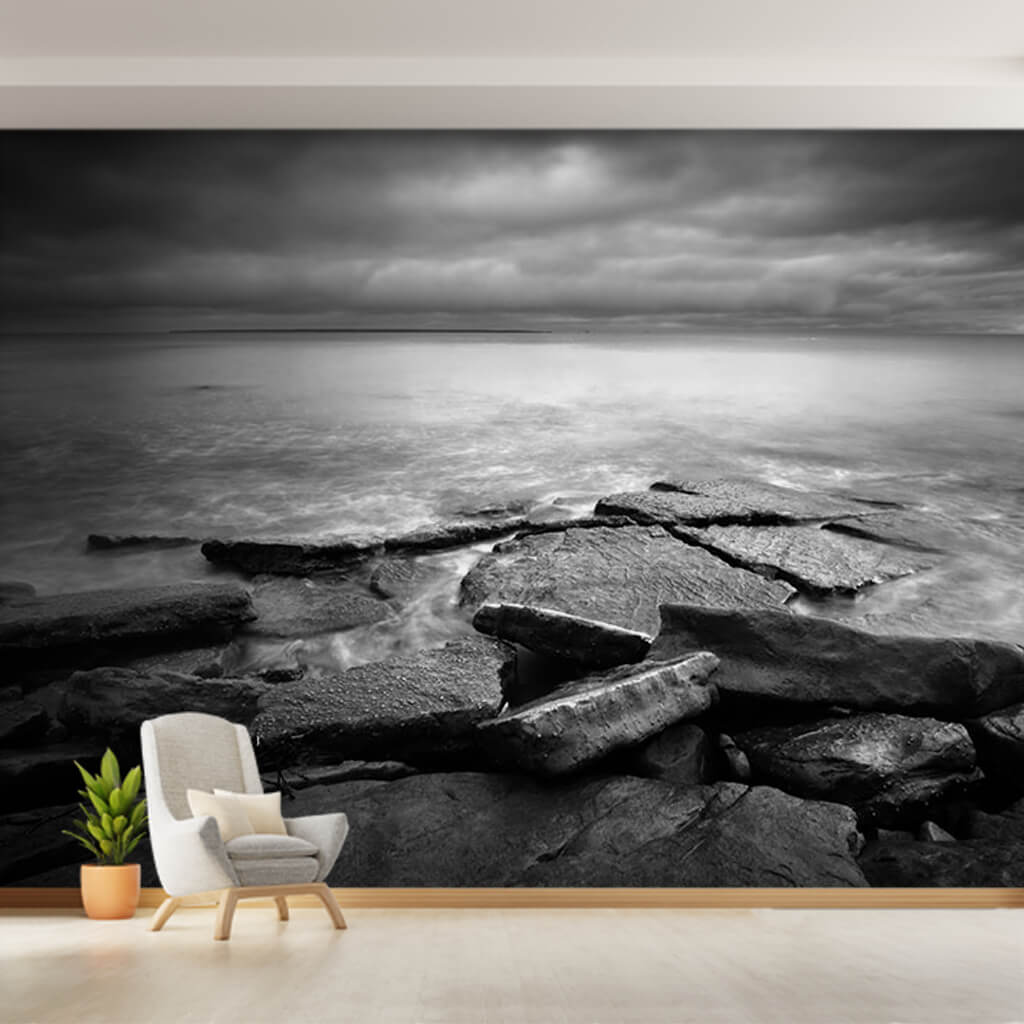 Cloudy sea and rocks on the beach black and white wall mural